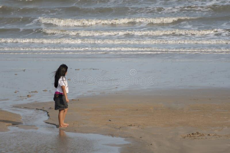 Uma posição da menina no mar na praia de Chao Samran, Phetchaburi, Tailândia foto de stock royalty free