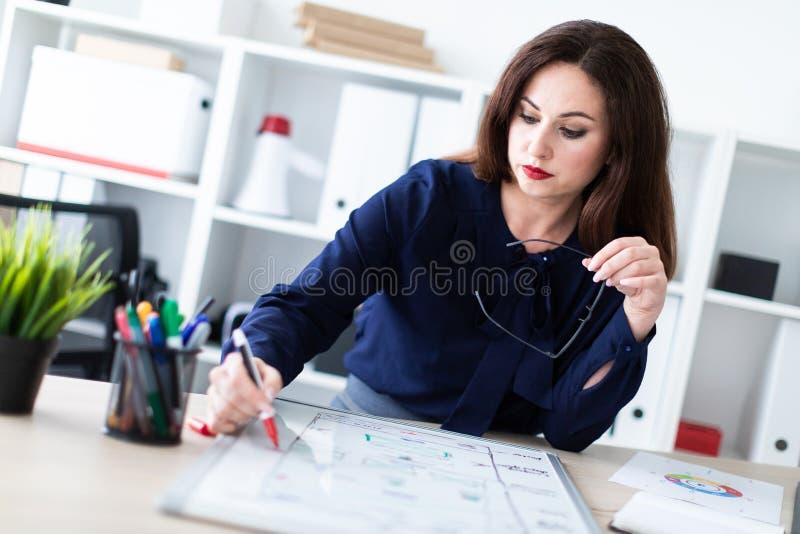 Uma posição da moça em uma tabela do computador e trabalho com uma placa magnética imagens de stock