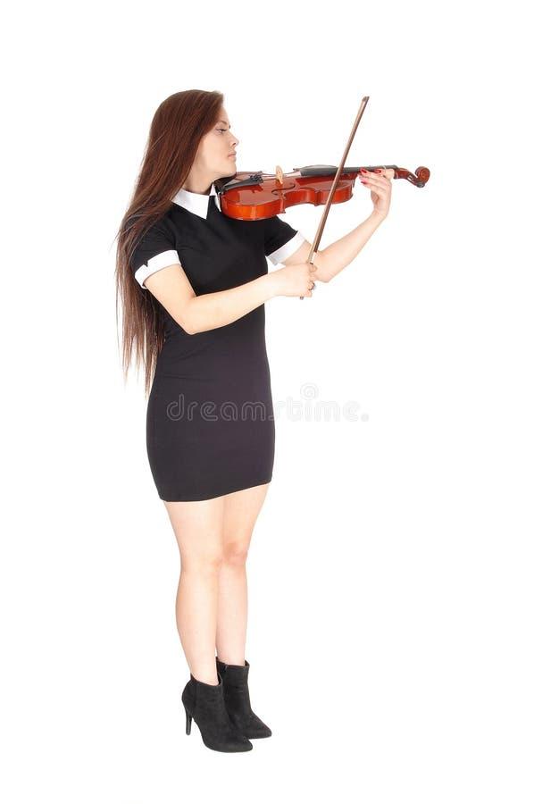 Uma posição da mulher e jogo do violino em um vestido preto foto de stock