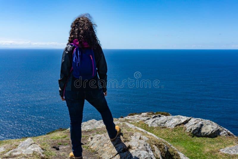 Uma posição da mulher na borda de um penhasco irlandês alto com o oceano no fundo imagem de stock royalty free