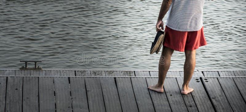 Uma posição descalça do homem no cais de madeira contempla o tran imagens de stock royalty free