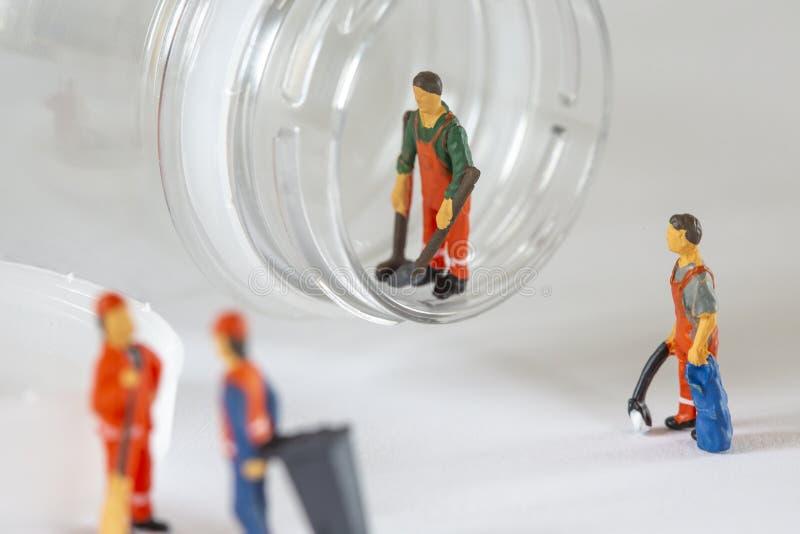 Uma posição diminuta do trabalhador na abertura de uma garrafa plástica fotografia de stock