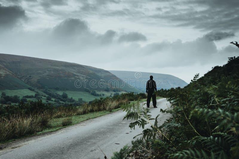 Uma posição do caminhante em uma estrada nas montanhas de Galês com uma composição misteriosa, sinistra imagem de stock