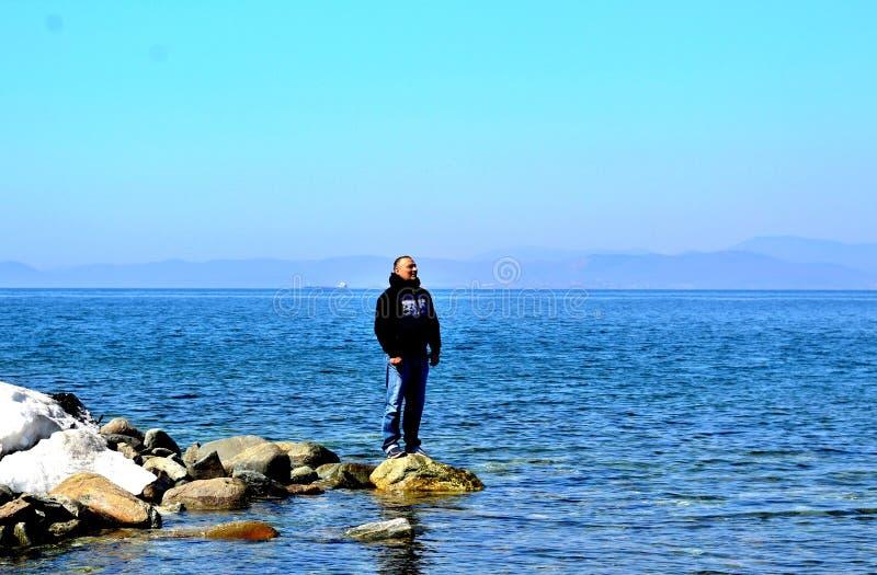 Uma posição do homem nas rochas contra o contexto do mar e da vista na distância imagem de stock