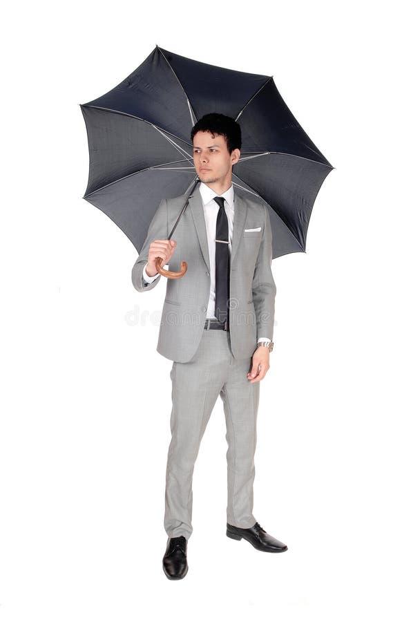 Uma posição do homem novo com um guarda-chuva aberto fotos de stock royalty free