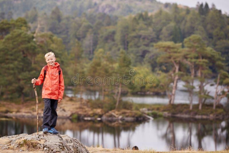 Uma posição do menino em uma rocha por um lago que guarda uma vara, sorrindo à câmera, distrito do lago, Reino Unido fotografia de stock royalty free