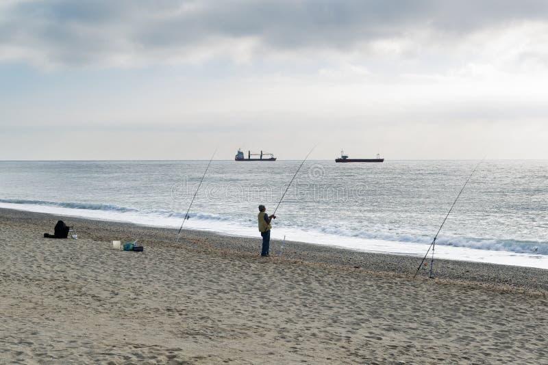 Uma posição do pescador com a vara de pesca em suas tentativas da mão a r imagens de stock royalty free