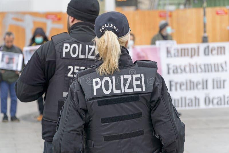 Uma posição fêmea alemão do agente da polícia na frente de um grupo de protestors fotografia de stock royalty free