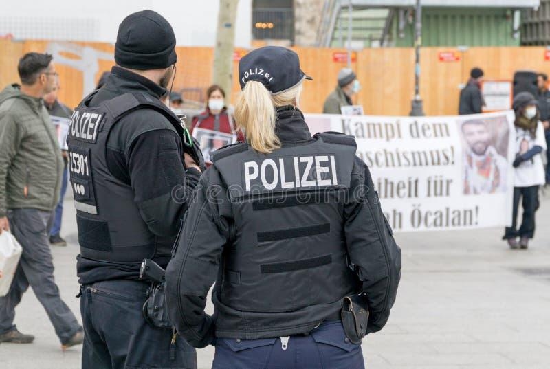 Uma posição fêmea alemão do agente da polícia na frente de um grupo de protestors imagens de stock royalty free