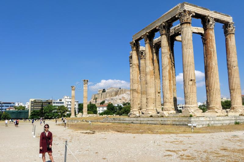 Uma posição fêmea nova do turista na frente do templo de Zeus abaixo da acrópole em Atenas, Grécia fotografia de stock royalty free