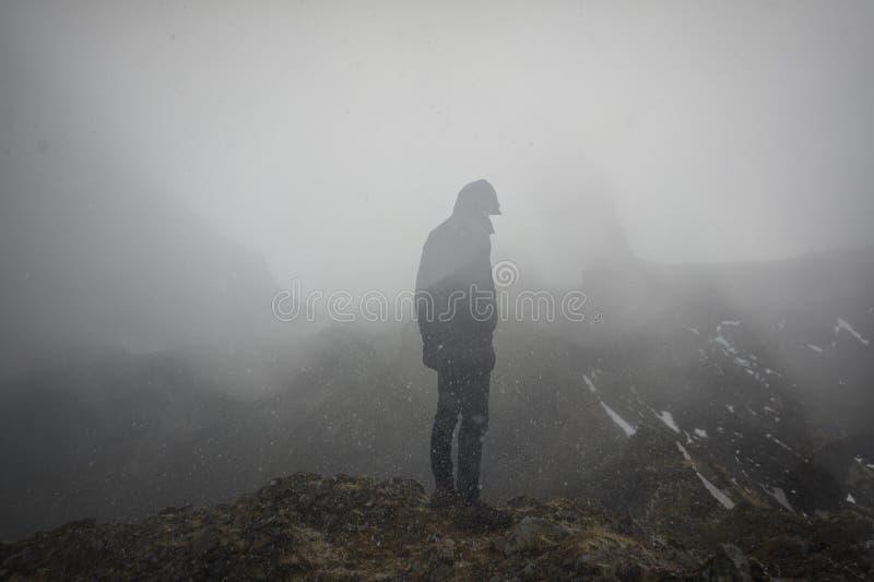 Uma posição fresca do homem na borda de uma montanha nevoenta fotografia de stock royalty free