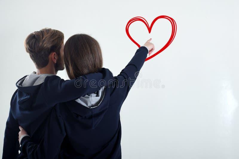 Uma posição nova dos pares que olha para trás a parede branca mostra ao coração imagens de stock royalty free