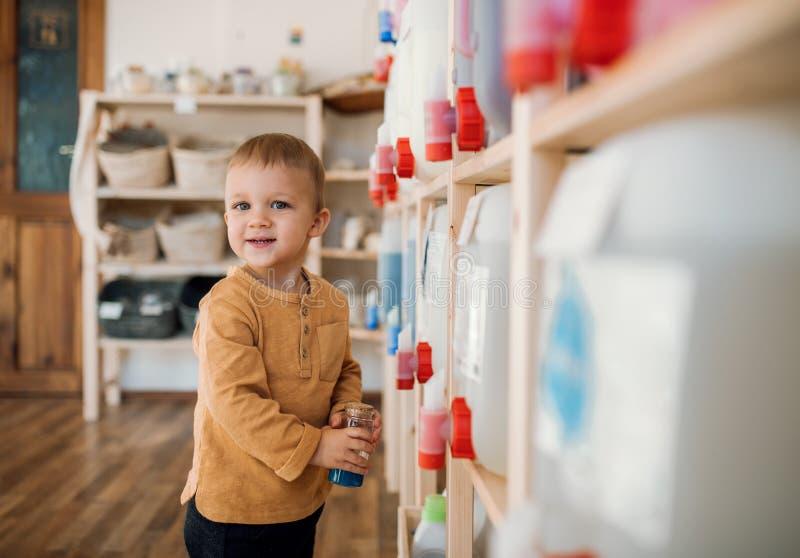 Uma posição pequena do menino da criança por distribuidores na loja zero do desperdício imagens de stock royalty free