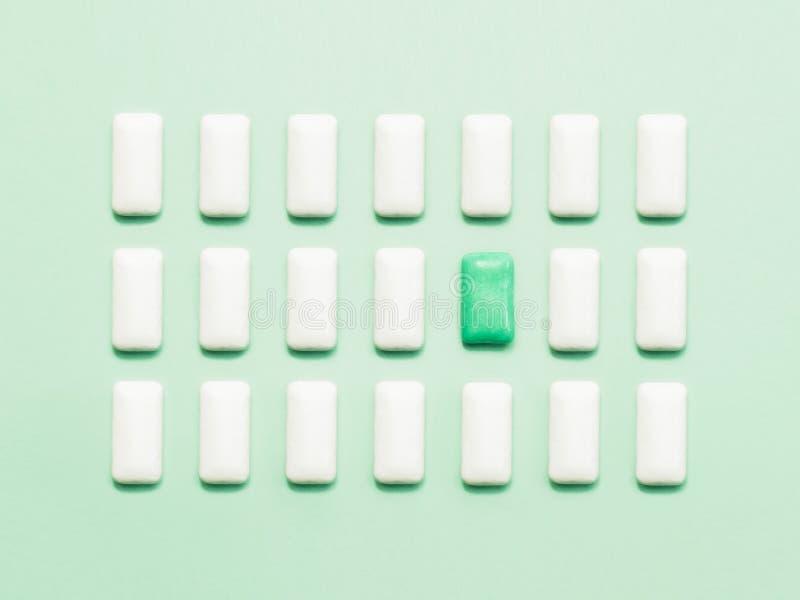 Uma posição verde da pastilha elástica fora das pastilhas elásticas brancas imagem de stock