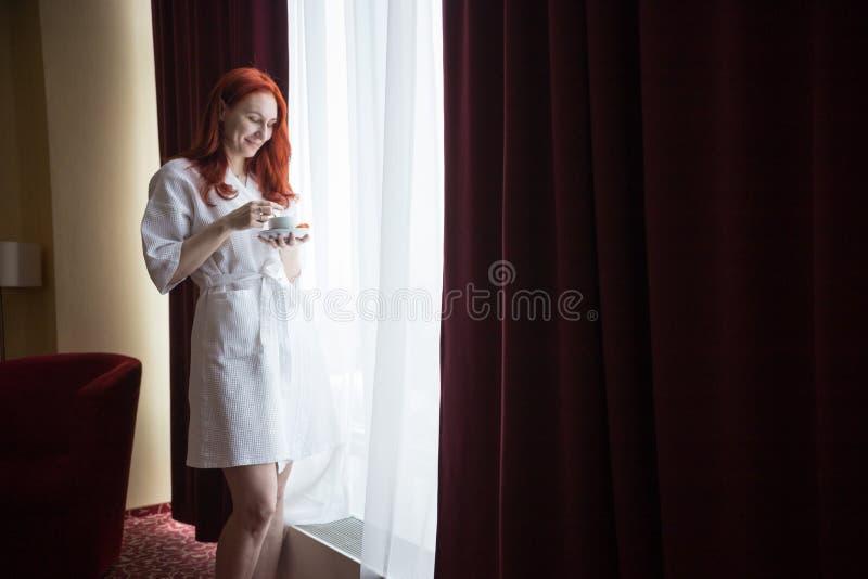 Uma posi??o da mulher do gengibre pela janela e guardar uma x?cara de caf? Olhando o copo fotografia de stock