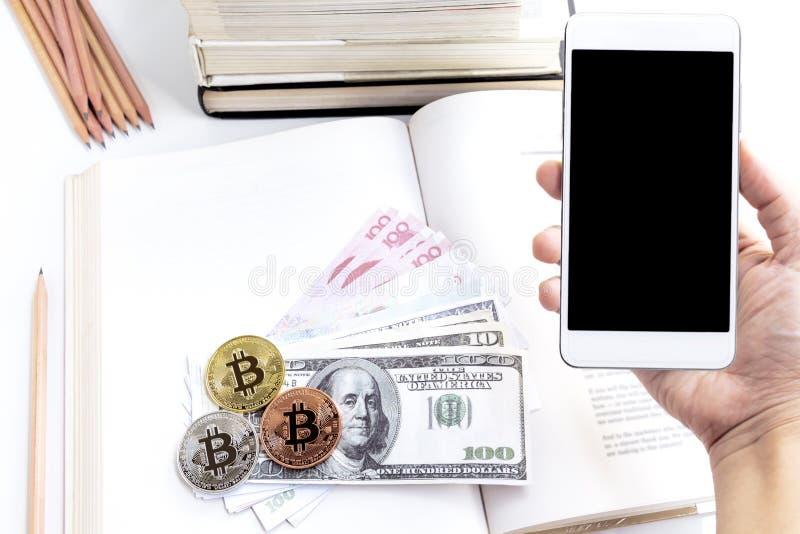 Uma posse da mão do ` s da mulher um smartphone com cédula e bitcoin no th imagens de stock royalty free