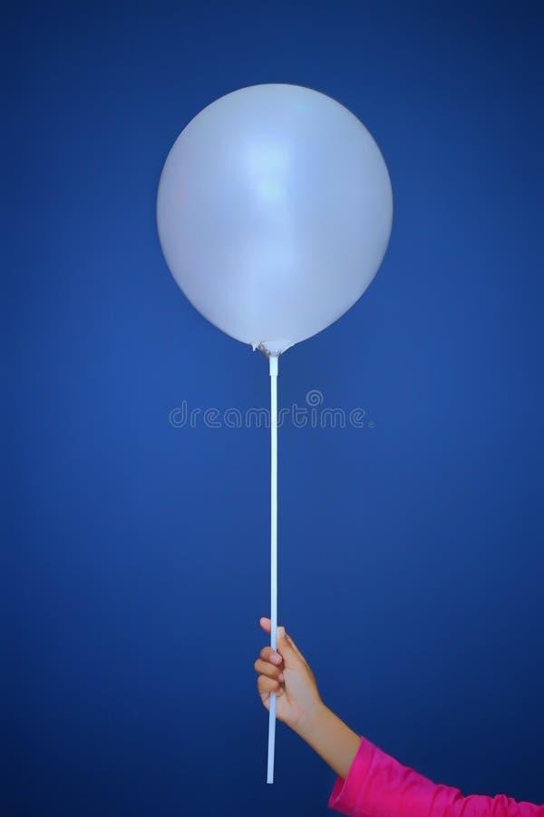 Uma posse da menina um ballon branco na frente de um fundo azul da cor foto de stock