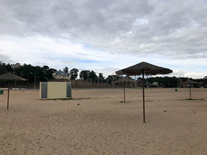 Uma praia abandonada vazia no mau tempo, outono frio na estação baixa com os guarda-sóis cobridos com sapê contra o céu azul fotos de stock