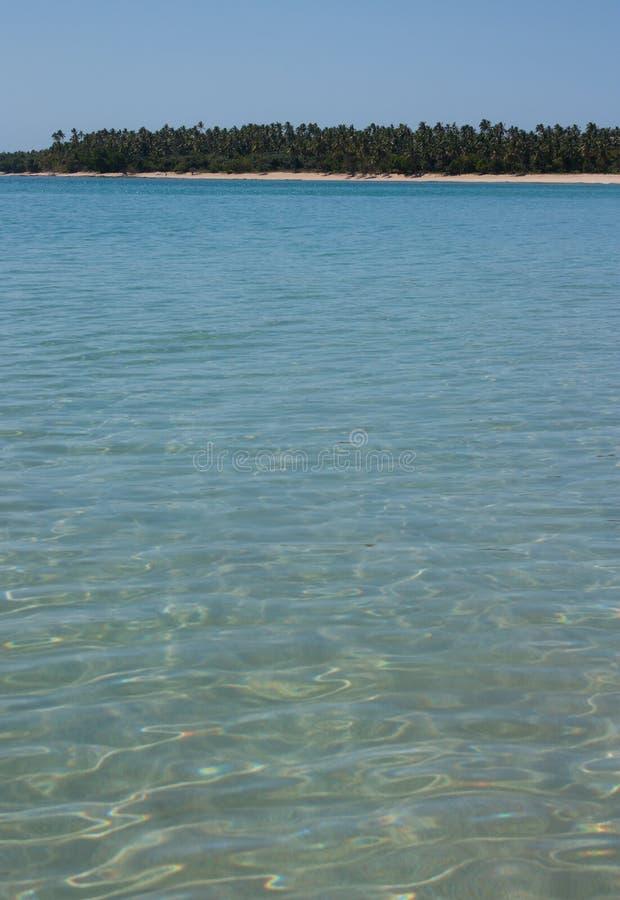 Uma praia com as árvores na distância e o mar em Tonga imagens de stock royalty free