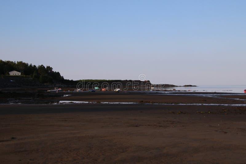 Uma praia na mar? baixa com um n?mero de barcos amarrados no que ? agora terra seca foto de stock