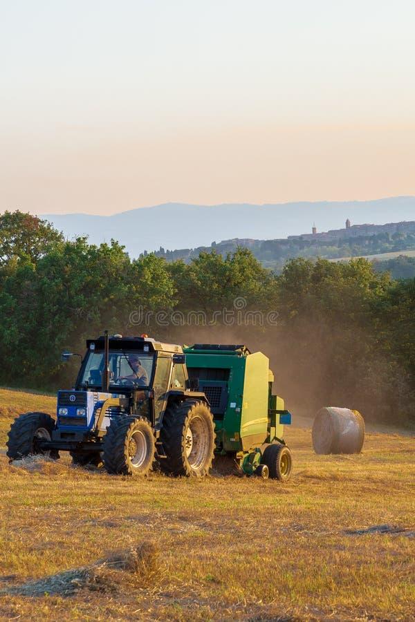 Uma prensa do feno no trabalho em um campo de Umbrian como o sol ajusta-se fotos de stock royalty free