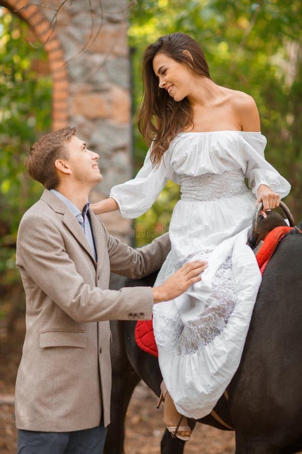 Uma queda nova em pares do amor em uma data exterior A mulher e o homem com o cavalo que anda no outono estacionam imagem de stock