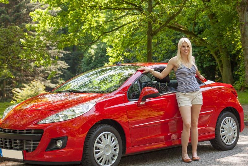 Uma rapariga com um carro vermelho fotos de stock royalty free