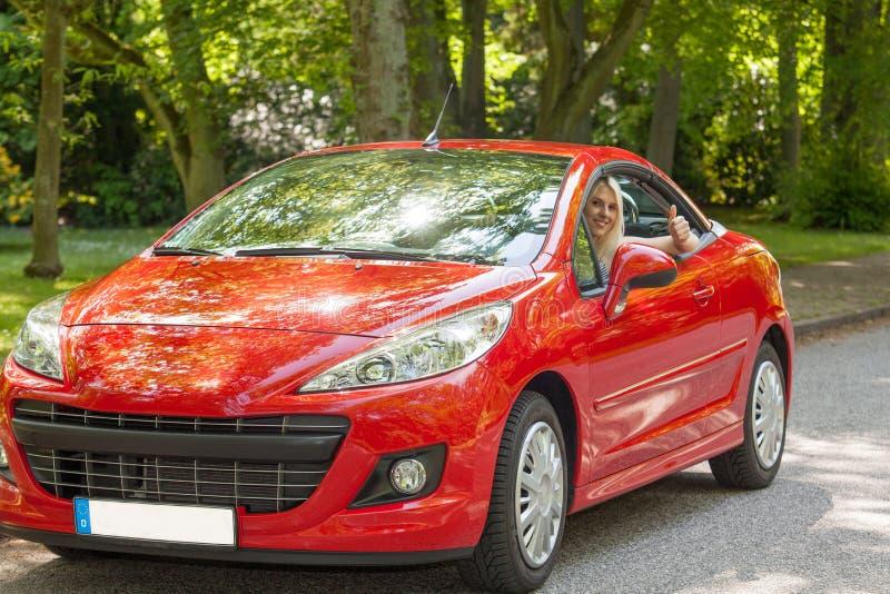 Uma rapariga com um carro vermelho imagem de stock