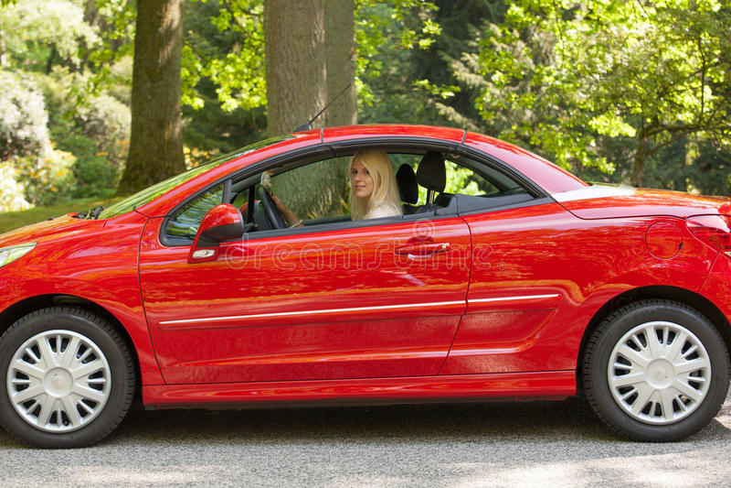 Uma rapariga com um carro vermelho foto de stock royalty free