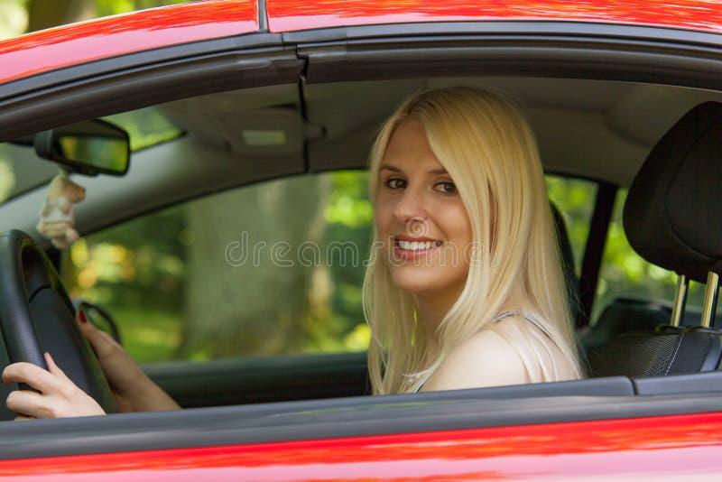 Uma rapariga com um carro vermelho imagens de stock royalty free