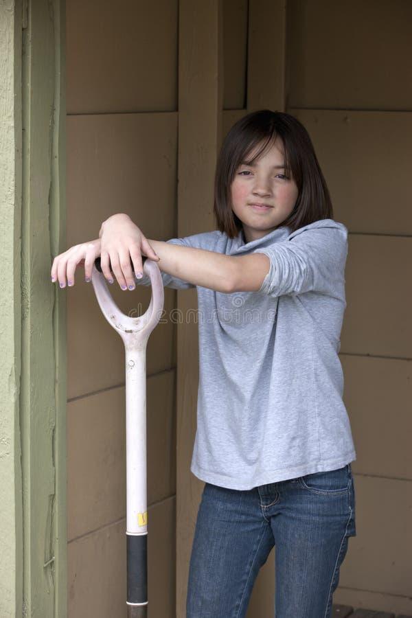 A menina tem os braços na pá. fotografia de stock royalty free