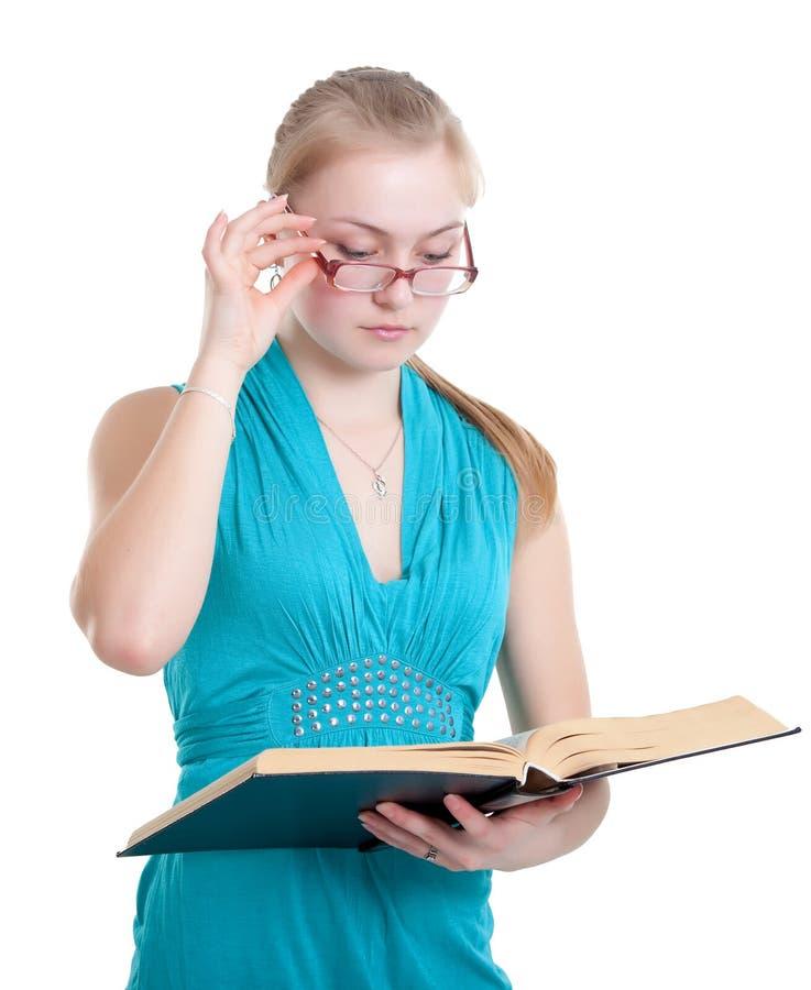 Uma rapariga nos vidros com um livro fotos de stock