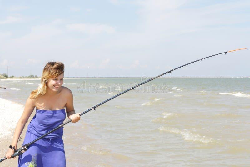 Uma rapariga trava um peixe fotografia de stock royalty free