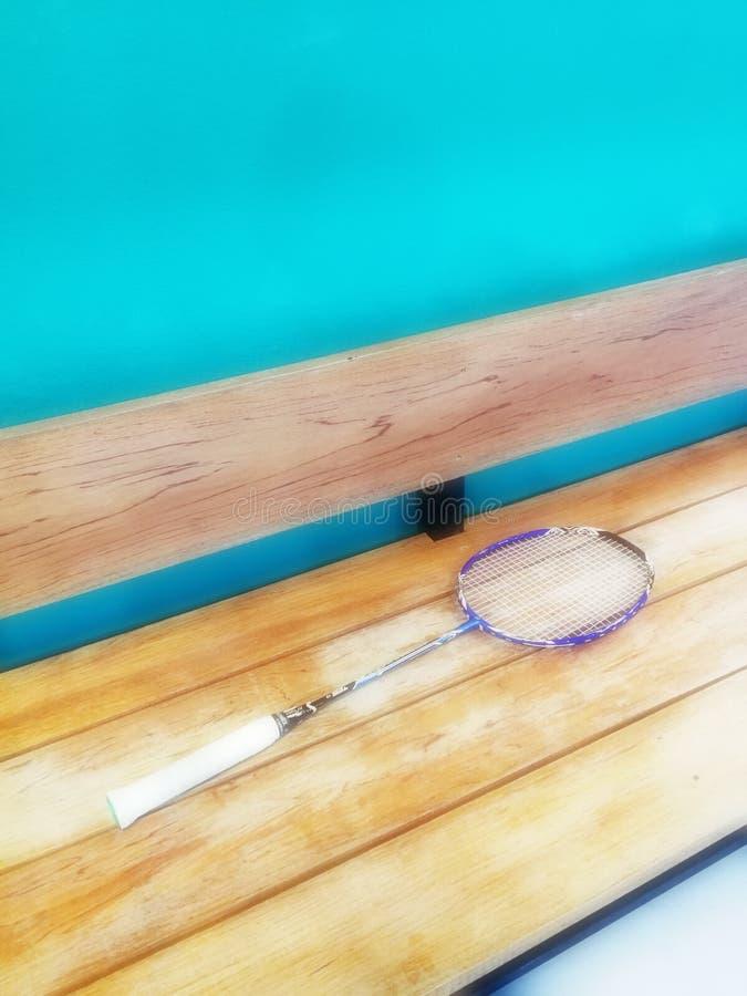 Uma raquete que põe sobre o banco de madeira no gym do badminton imagem de stock royalty free