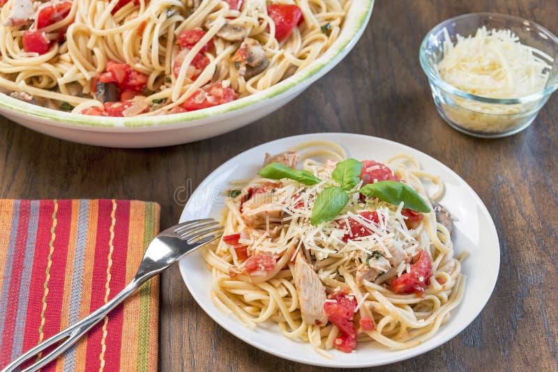 Uma refeição com linguine da galinha, da manjericão e do tomate fotografia de stock royalty free