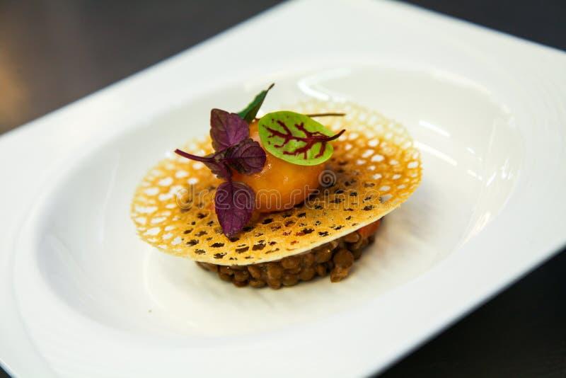 Uma refeição das lentilhas, do ovo cozido e das ervas em uma placa branca imagem de stock