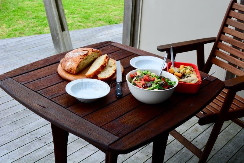 Uma refeição saudável entusiasta com pão recentemente cozido caseiro, salada do legume fresco e algum guisado de galinha, serviu  fotografia de stock