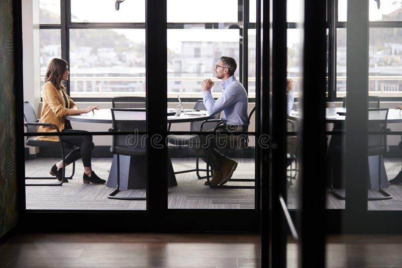 Uma reunião para uma entrevista de trabalho, comprimento completo do homem de negócios e da jovem mulher, parede de vidro complet fotografia de stock royalty free