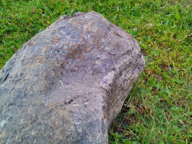Uma rocha ao lado do gramado foto de stock