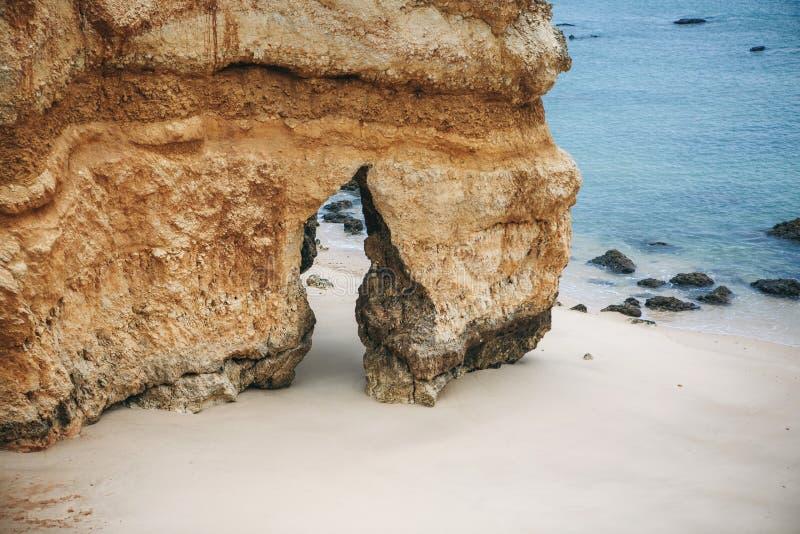 Uma rocha com uma fenda na praia fotografia de stock