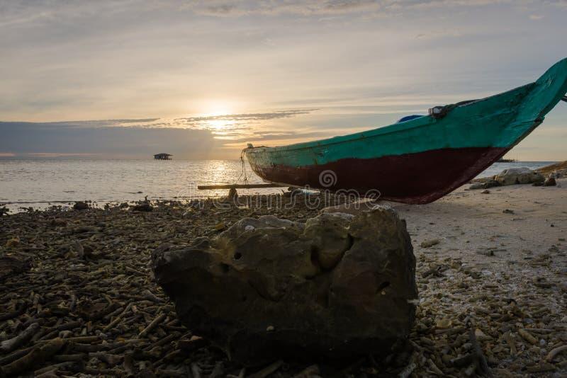 Uma rocha e um barco de pesca em uma praia rochosa na ilha de Harapan com o céu bonito do nascer do sol ou do por do sol imagens de stock royalty free