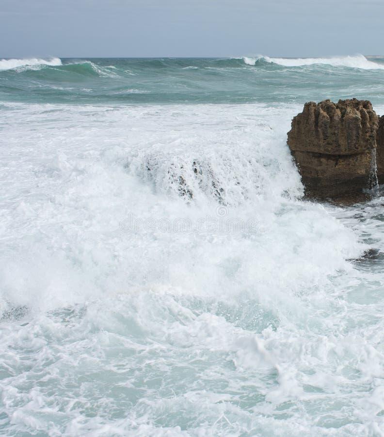 Uma rocha e um mar espumoso e ondulado na grande estrada do oceano em Austrália fotos de stock royalty free