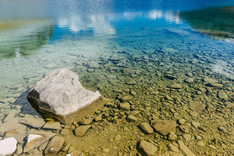 Uma rocha em um lago com água azul transparente nos cumes franceses foto de stock