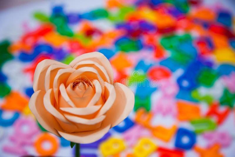 Uma rosa de papel colocada em blocos coloridos do alfabeto imagens de stock
