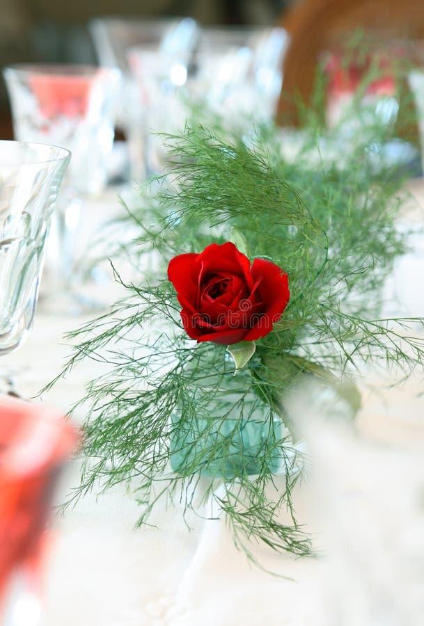 Uma rosa em uma tabela de jantar foto de stock