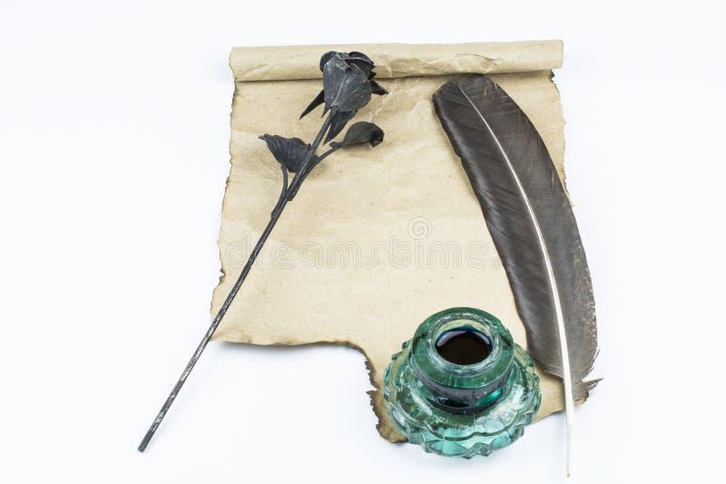 Uma rosa feita do metal e uma mentira escura do pena e a verde do tinteiro em uma folha de papel limpa isolada no fundo branco imagens de stock royalty free