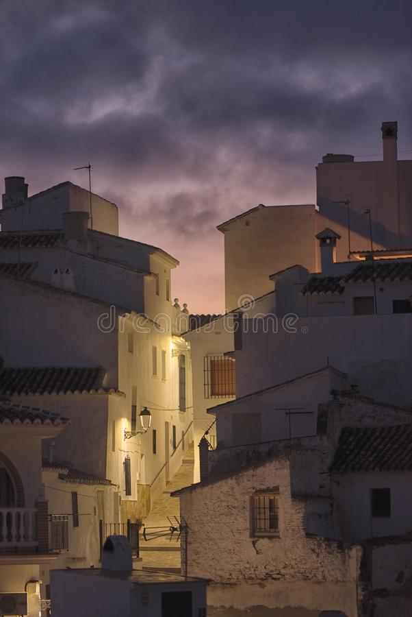 Uma rua espanhola quieta no crepúsculo como as luzes aproxima-se Sedella, Espanha imagens de stock royalty free