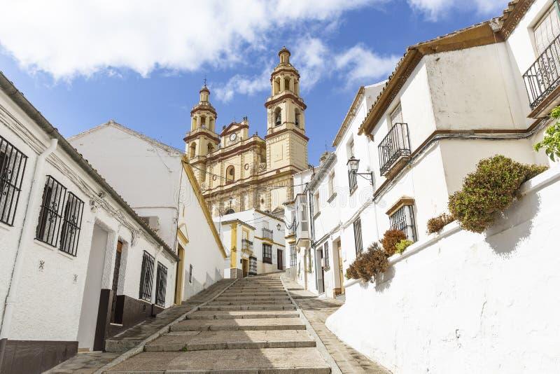 Uma rua na cidade de Olvera e na nossa senhora da igreja da encarnação imagens de stock