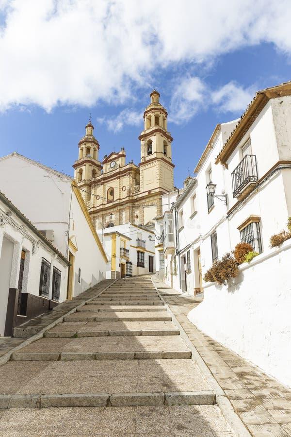 Uma rua na cidade de Olvera e na nossa senhora da igreja da encarnação fotos de stock