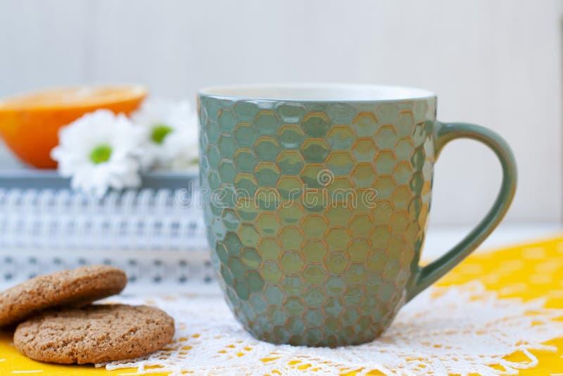 Uma ruptura do estudo: um copo do ch?, das cookies e de uma metade de uma laranja foto de stock royalty free